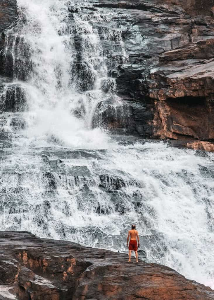 woman in orange tank top sitting on rock near waterfalls
