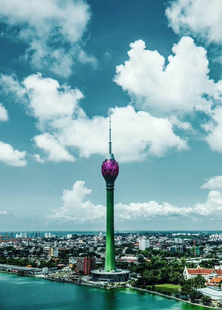 green and pink tower under blue sky and white clouds